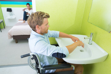 Disabled man washing hands at sink