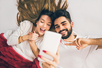 Selfie! Top view of beautiful young loving couple lying in bed and making selfie