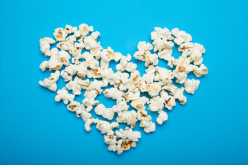 Heart made of delicious popcorn on a blue background.