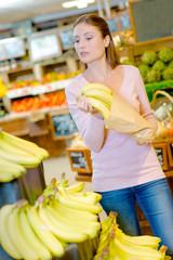 woman putting banana inside a paperbag