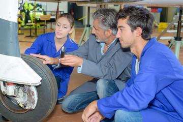 apprentice aircraft mechanicians maintaining airplane