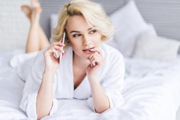 beautiful blonde girl talking by smartphone and looking away in bedroom