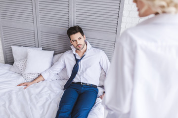 selective focus of handsome man lying on bed and looking at girlfriend