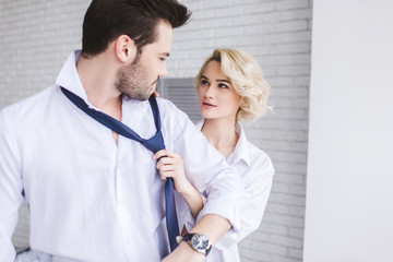 young couple looking at each other while woman holding necktie of handsome boyfriend