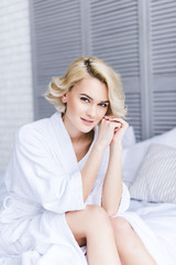 beautiful blonde woman in bathrobe sitting on bed and smiling at camera