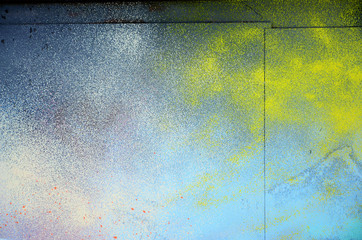 A large fragment of the graffiti pattern applied to the wall with aerosol paint. The gradient between several colors is carried out by spraying the paint. Abstract background image