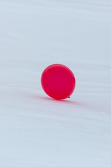 one red balloon on white snow ground in winter