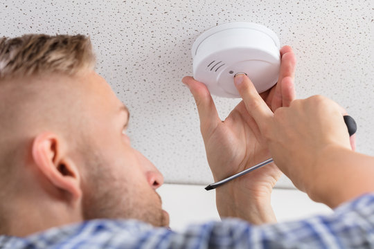 Person's Hand Installing Smoke Detector On Ceiling