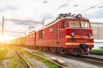 Red locomotive electric with a freight train at high speed rides by rail.