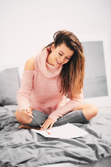 Girl painting with wather color and sitting on the bed in the morning