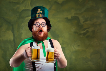 A fat man with a beard in St. Patrick's suit is smiling with a mug of beer on a green background.