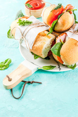 Fresh baguette sandwich with bacon, cheese, tomatoes and spinach, light blue background copy space