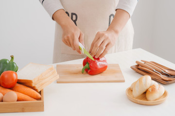 Male hands slicing fresh red bell peppers