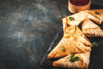Asian food. Vegetarian samsa (samosas) with tomato sauce. Dark blue background copy space