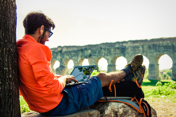 Backpacker sitting on a rock under a tree writing on laptop in front of ancient roman aqueduct. Young attractive athletic man with orange sportswear and backpack in acquedotti Park in Rome