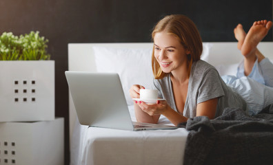 young beautiful woman with  laptop and  cup of coffee in   morning in bed