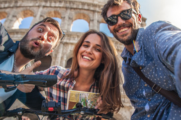 CAMERA POV Three happy young friends tourists with bikes and backpacks at Colosseum in Rome taking selfies pictures with smartphone having fun. Lens Flare.