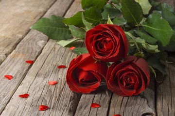 Red roses on old wooden table with confetti hearts, Valentine's day