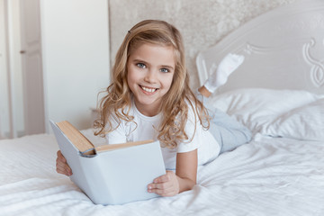 smiling kid lying on bed with book and looking at camera