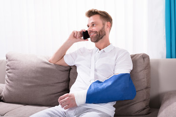 Man With Fractured Hand Talking On Mobile Phone