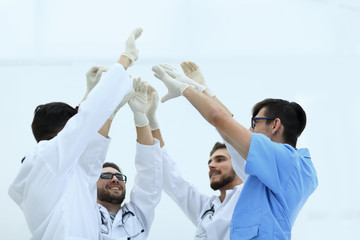 surgical team raising their hand