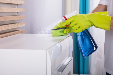 Person Cleaning Furniture With Spray Bottle