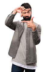 Handsome man with beard focusing with his fingers on white background