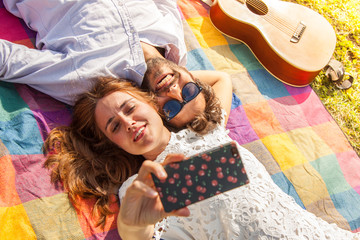 Happy beautiful girl with white dress and attractive man with sunglasses taking selfies with smartphone lying on colorful blanket on grass. Young couple with guitar on sunny summer day.