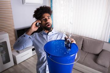 Man Calling Plumber While Leakage Water Falling Into Bucket