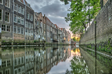 View at sunset of a canal in downtown Dordrecht, The Netherlands with houses built directly on the waterside