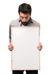 Handsome man with beard holding an empty placard on white background