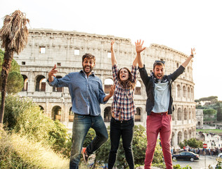 Three young friends tourists taking photos jumping in front of colosseum with dslr camera timer in rome at sunset.
