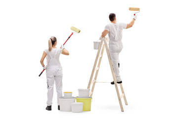 Female painter and a male painter climbed up a ladder painting