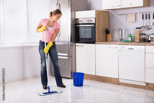 Ordinaire Young Woman Cleaning Kitchen Floor With Mop