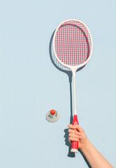 Woman's hand holding a retro badminton racket