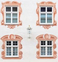 Bemalte Hauswand mit vier Fenstern und Laterne