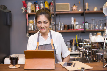 Asian barista woman using tablet for promote shop. Woman using tablet with attractive smiling.