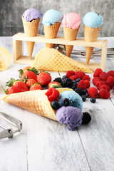 Set of ice cream scoops of different colors and flavours with blueberries, raspberries and blackberries.