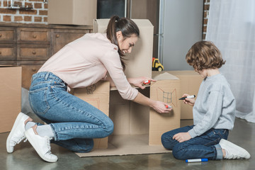 happy mother and son drawing on cardboard box while moving home