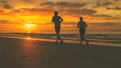 Silhouettes of couple who are running on the beach at sunrise.