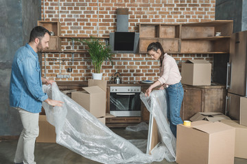 young couple packing picture during relocation