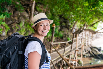 portrait of a smiling happy woman with a backpack hiking in the journey