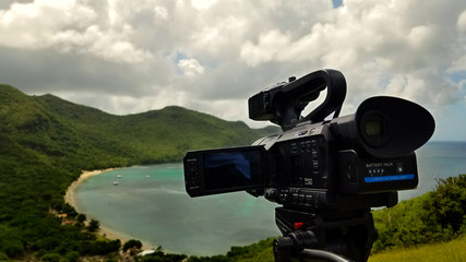 Video camera on the tripod at the top of mountain of tropical island.