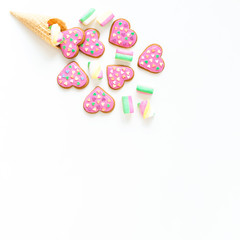Gingerbread cookies with pink glaze and marshmallow in waffle cone on withe background. Holiday concept. Flat lay. top view.