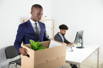 Businessman Moving Out With Cardboard Box From Office