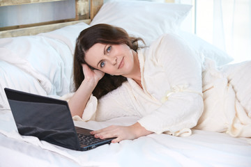 Beautiful girl. Work at home. Black notebook. White Bed