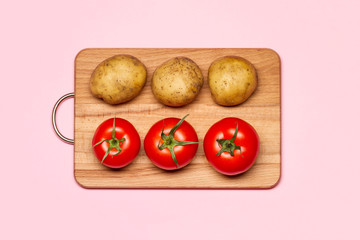 Healthy Eating. Three Fresh Potatoes Near Three Tomatoes On A Wooden Chopping Board