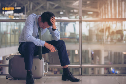 Businessman sitting on luggage at the  terminal airport alone, unhappy trip by delay flight.