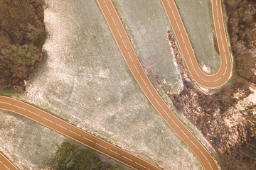 Aerial Top View Of Winter Forest And Winding Countryside road with a little bit of snow