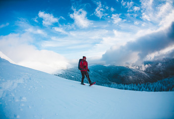 A man in snowshoes in the mountains.